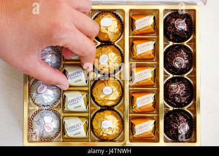 Paphos, Cyprus - November 20, 2016 Woman hand taking candy Ferrero Tenderly from box of Ferrero candies. - Stock Photo