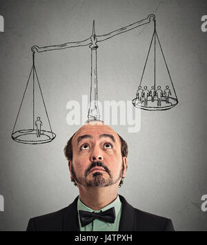 businessman with scale above head one man weighting more than group off business people on a balance. Power, opinion, - Stock Photo