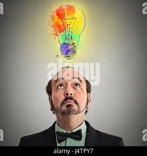 Concept of Creative business idea with colorful lightbulb. Portrait middle aged businessman came up with solution answer for problem looking up isolat