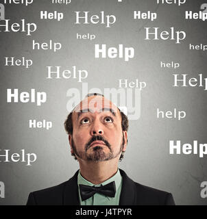 Closeup headshot man looking up for help isolated on grey wall background - Stock Photo