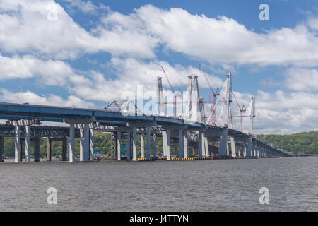Tower cranes work to complete the cable towers on New Tappan Zee Bridge over the Hudson River between Westchester - Stock Photo