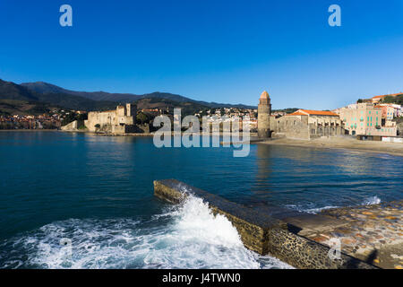 Collioure town in Languedoc-Roussillon, Southern France is pictured from the town pier. A wave is breaking against - Stock Photo