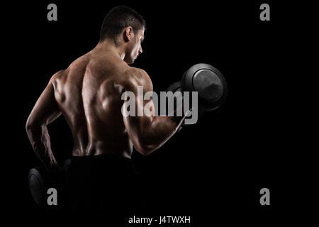 Athletic man training biceps on black background - Stock Photo