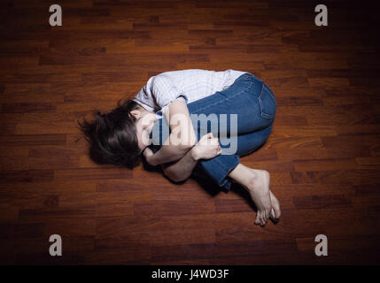 Lying on the floor of a lonely young woman in a empty room - Stock Photo