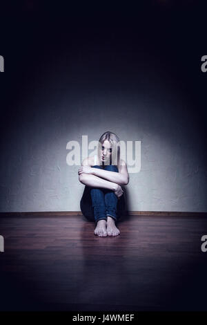 Young sad woman sitting alone on the floor in an empty room - Stock Photo