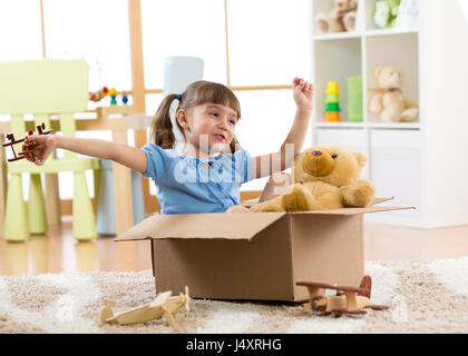 Child playing with plane toy at home. Travel, freedom and imagination concept. - Stock Photo