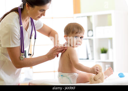 doctor examining kid by touch in medical office - Stock Photo