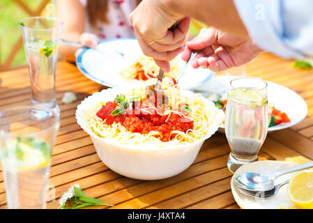 Family dinner variety of Italian dishes on wooden table in the garden - Stock Photo
