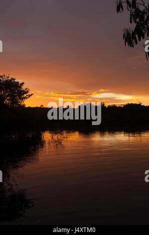 Partially overcast orange sunset over the River Amazon with ripples in the water surface radiating out - Stock Photo