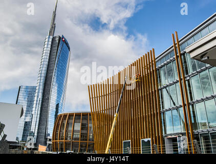 a couple of workers, working on aerial platform for a new construction near Unicredit tower in Milan downtown - Stock Photo