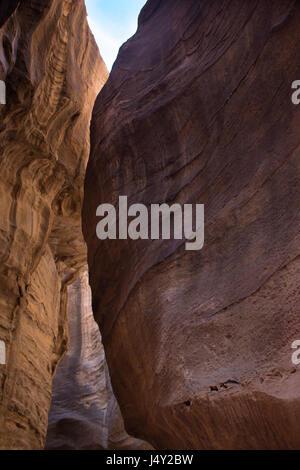 The steep walls of Al Siq, the caravan passageway in Petra, Jordan, leading to the Treasury. The narrow, high walled - Stock Photo