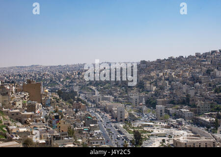 View of Amman's modern and older buildings including the Roman Theater below from the hill of Amman Citadel. Hazy - Stock Photo