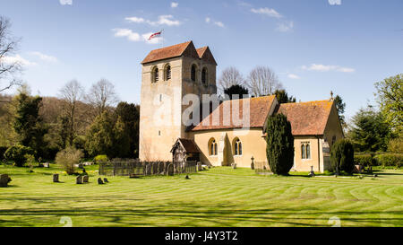 Sun shines on the tower of the 12th century Norman church of St Bartholomew in the village of Fingest, nestled under - Stock Photo