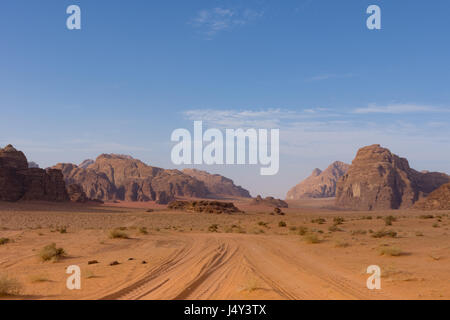 Four wheeling road through orange or rust colored sand with rugged mountains in the distance with deep blue sky - Stock Photo
