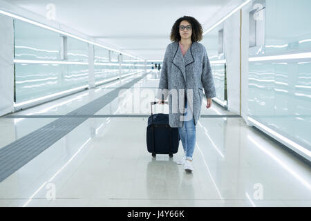 Black woman holding luggage ready to leave for travel - Stock Photo