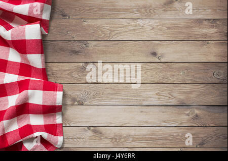 red picnic tablecloth on wood table background - Stock Photo