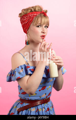 Cheeky pin up style shot of woman drinking milk - Stock Photo