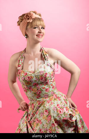 Cheeky pin up style shot of woman wearing vintage style clothing on a pink background - Stock Photo