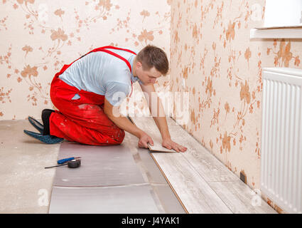 young handyman installing wooden floor in new house - Stock Photo