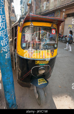 Cityscape reflected in the widhield of a tuk tuk parked on the street in Jodhpur, India - Stock Photo
