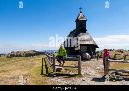 Happy smiling hikers resting near small mountain church in mountain nature on sunny day, Velika planina, Slovenia, - Stock Photo