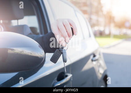 Man seated in his car holding the key - Stock Photo
