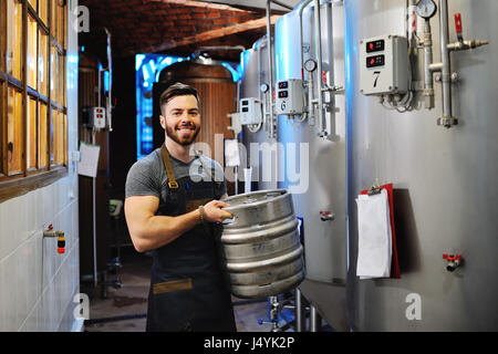 Man with a beard working in uniform with a barrel of beer in a brewery with metal containers in the background - Stock Photo