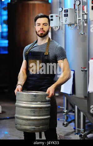 Male brewer with a metal beer barrel on the background of the brewery - Stock Photo