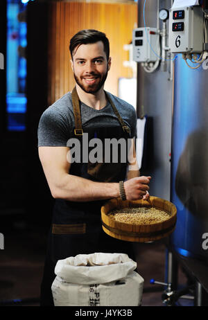 Cute young bearded man working beer factory in apron with malt in hands on a background of metal beer tanks - Stock Photo