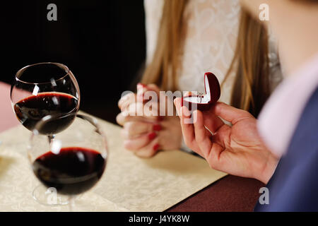guy doing the girl proposal in restaurant. man gives a woman an  - Stock Photo