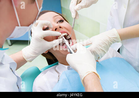 Closeup portrait dentist, his assistant carrying out thorough examination dental procedure, tooth extraction on - Stock Photo