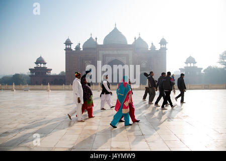Group of Tourists in colourful clothing at Taj Mahal complex in Agra, India - Stock Photo