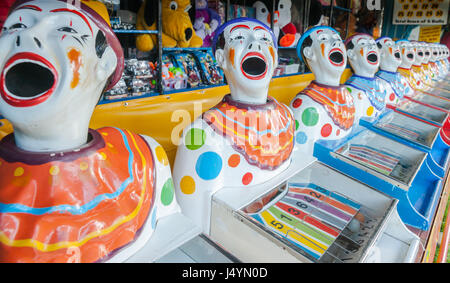 A row of sideshow carnival game clowns with mouths open diminishing into distance. - Stock Photo