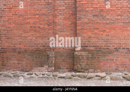 Grunge red brick wall and stone pavement . Urban background - Stock Photo