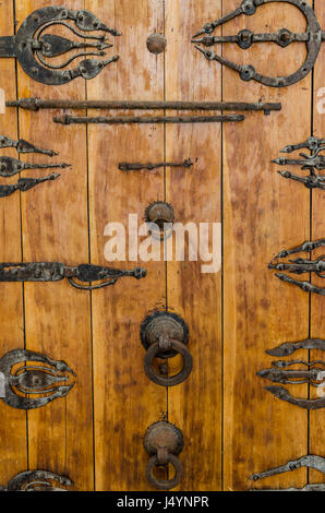 Ancient wooden door with metal fittings, handles and ornaments at historic building in old arabic town Fez, Morocco. - Stock Photo