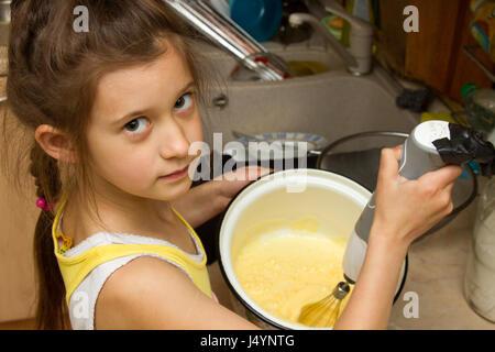 Child preparing cookies in kitchen. - Stock Photo