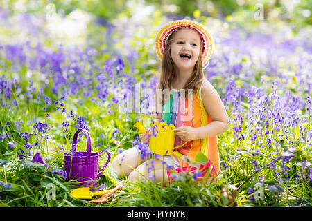 kid in bluebell woodland child with flowers garden tools and wheelbarrow girl gardening