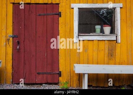Rust Red Door On Golden Yellow Barn With Bench In Sweden   Stock Photo
