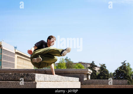 Young man jumping over the wall. Parkour in the urban space. Sports in the city. Sport activity. - Stock Photo