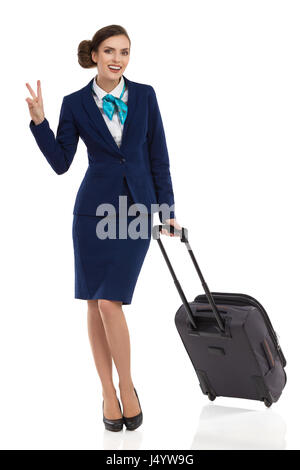 Smiling businesswoman in blue formal wear is standing with trolley bag, showing peace sign and looking at camera. - Stock Photo