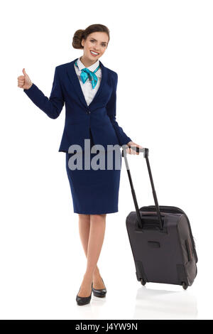 Smiling stewardess woman in blue suit and skirt is standing with trolley cabin baggage, showing thumb up and looking - Stock Photo