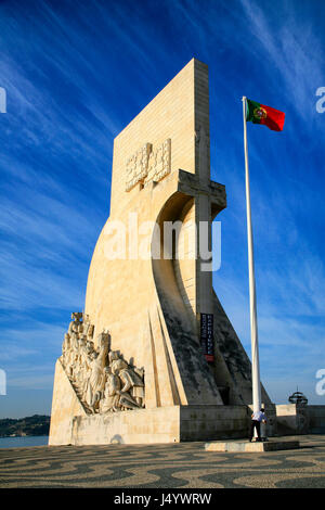 Padrão dos Descobrimentos on the banks of the River Tagus with a man hoisting a flag in Lisbon, Portugal. - Stock Photo