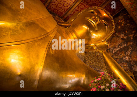 Close-up of the giant golden statue at the Temple of the Reclining Buddha in Bangkok, Thailand - Stock Photo