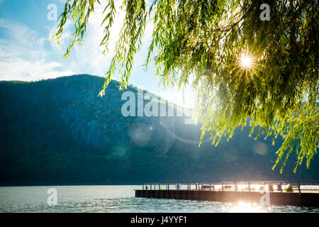 River, mountains and dock with sun shining through the trees from Cold Spring NY - Stock Photo