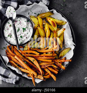 Two sorts of oven potatoes with herbal quark - Stock Photo