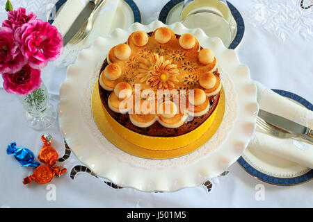 Simnel cake - traditional Easter fruit cake decorated with marzipan on a table set for tea. - Stock Photo