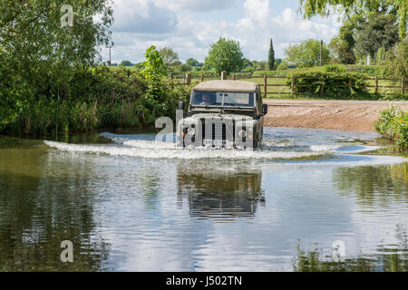 Model released image of a man driving a 1973 ex army Land Rover Series 3 Long Wheel Base into the river VER which - Stock Photo