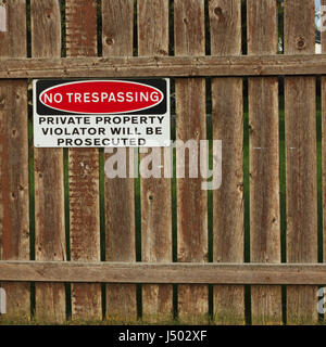 A no trespassing sign on a fence. - Stock Photo