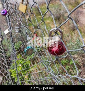 Locks hanging on a bridge fence. - Stock Photo