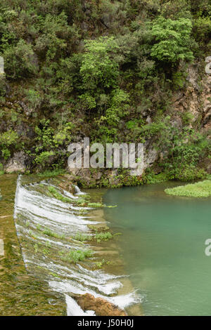 Mountain river with small waterfall and trees growing in rocks - Stock Photo
